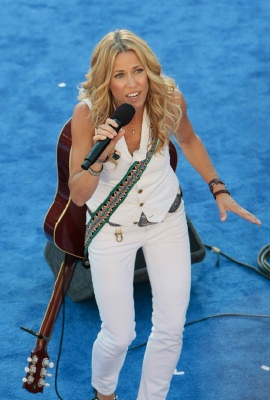 sheryl crow in white suit singing on blue stage