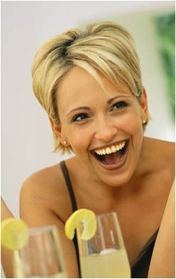 smiling girl with drink leaning forward to listen