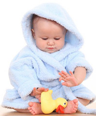 baby in blue hooded bathrobe playing with rubber ducky