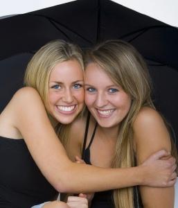 two smiling friends huddled up under a large black umbrella
