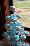 cupcake stand with white cupcakes and blue sprikles