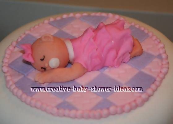 closeup of baby sleepeing on a pink a purple blanket cake