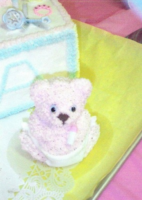 closeup of baby teddy bear cake sitting next to baby block cake