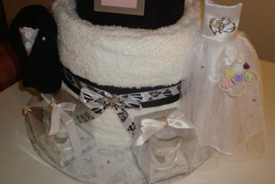 2nd layer of towel cake with tux and wedding dress decorations