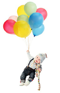 baby with scarf and hat floating holding onto colorful balloons