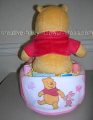 back of blanket winnie the pooh diaper cake showing baby bib