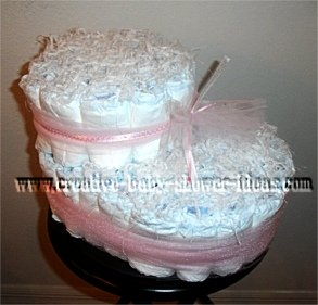 white baby bootie diaper cake tied with pink tulle