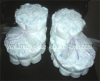 white baby bootie diaper cake with purple tulle