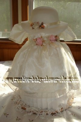 cream vintage baby dress and hat over a diaper cake