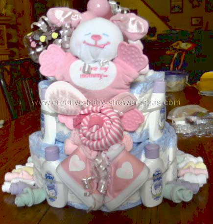 lavender and pink baby cake with pink baby teether toy, sneakers and washcloth shaped like a baby