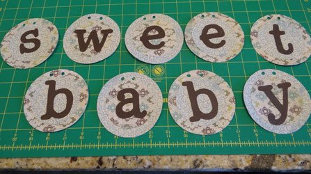 baby shower banner circles with hole punches in top of circles