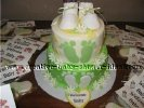green and yellow cake with green footprints and white baby booties surrounded by favors