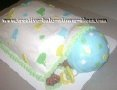 sleeping baby on its belly cake covered with white blanket and blue hat