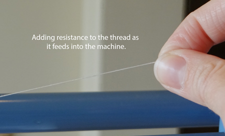 adding resistance to thread as it goes into the machine