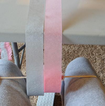 wooden dowel threaded on crepe paper rolls sitting on legs