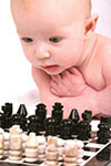 baby intently watching a game of chess