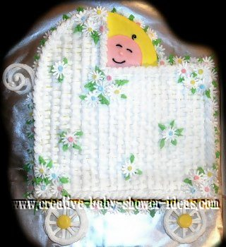 white basket weave baby carriage cake with smiling baby peeking out