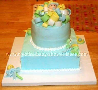 2 tier baby boy cake with fondant bow on top and baby boy with pacifier