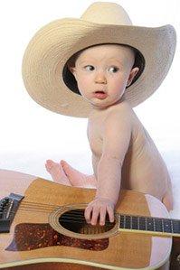 baby wearing cowboy hat sitting next to guitar
