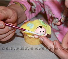 painting the baby pacifier for the shower cupcakes