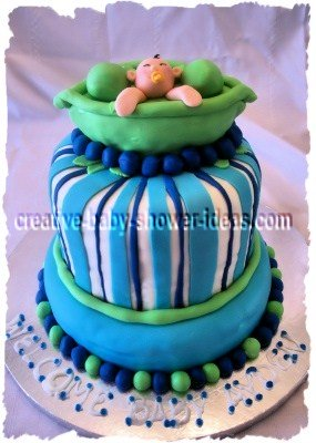 green and blue pea in the pod baby shower cake with baby peeking out of pea pods on top