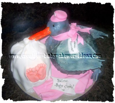 grey carved stork shower cake with pink scarf and baby wrapped in white blanket
