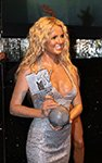 britney spears in gown smiling while holding mtv award