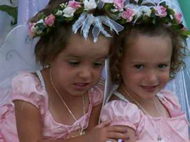 2 smiling girls with flower head wreaths and butterfly wings