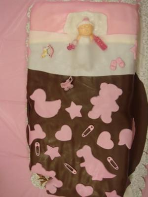 baby sleeping on pink and brown baby shower cake