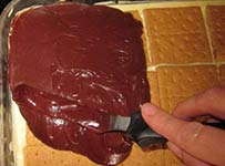 spreading frosting on chocolate eclair cake