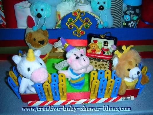 closeup of animal ride car infront of diaper cake made with supplies and stuffed animals