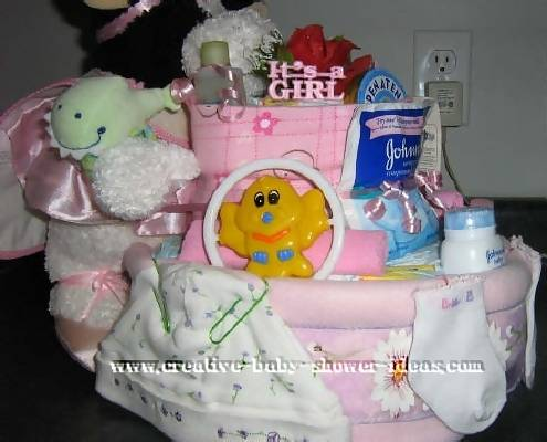 side of cow diaper cake showing pink and white decorations