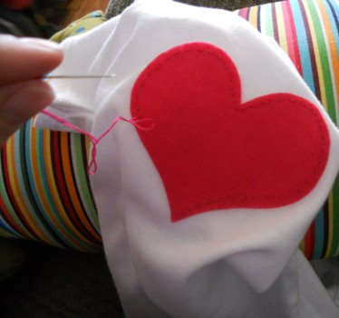 sewing applique heart onto baby onesie