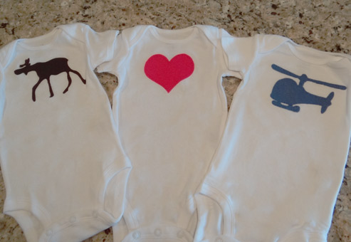 applique heart, helicopter and moose onesies on counter