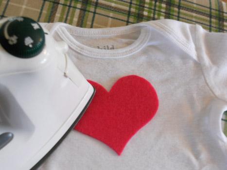 applique heart being ironed onto onesie