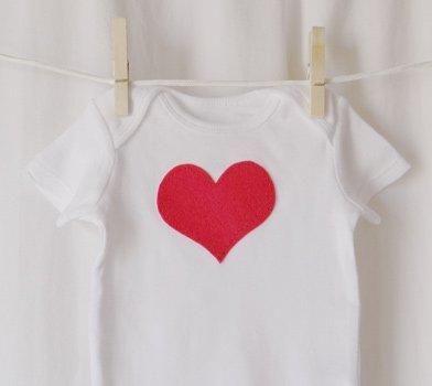 finished pink heart onesie hanging on clothesline