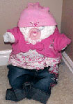 diapers rolled into a baby with a cute pink and blue outfit and pink pacifier
