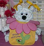 white diaper bear made out of rolled diapers with yellow hair bows and a cute pink flower bib