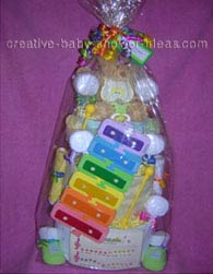 teddy bear and xylophone diaper cake wrapped in cellophane
