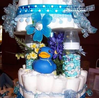 closeup of bottle pillars filled with m&ms on diaper cake