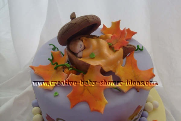 closeup of baby sleeping in acorn on top of cake using a leaf as a blanket