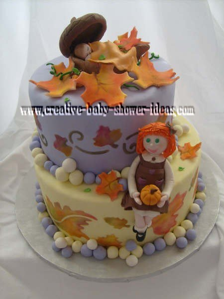 fall leaf baby shower cake with baby sleeping in acorns on top