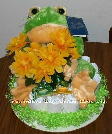 frog diaper cake with flowers and pacifiers