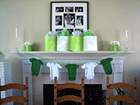 picture taken at a baby shower with a white fireplace with green and white onesies on a clothesline in front and green and white gift bags on top