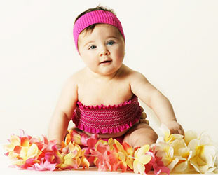 baby in pink tube top and headband surrounded by hawaiian flowers
