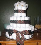 cowboy diaper cake with brown and teal polka dot ribbon and white flowers on top