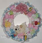 diaper wreath with pink baby items and cream dog