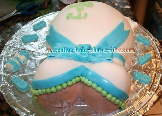 top view of  pregnant belly cake showing green necklace