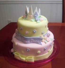 yellow and pink princess baby shower cake with purple and white crown on top