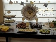 baby shower food table with book wreath and hanging book decorations